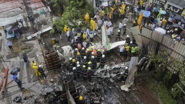 Rescuers stand amid the wreckage of a private chartered plane that crashed in Ghatkopar area, Mumbai.