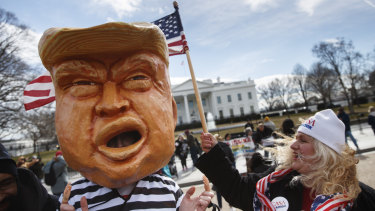 A person dressed up as President Donald Trump in a prison uniform in front of the White House.