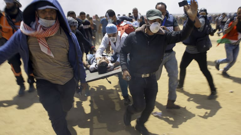 Palestinian medics and protesters evacuate a wounded youth from the clashes in Gaza.