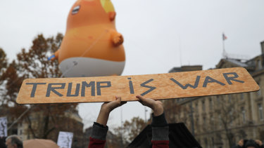 An anti-Trump placard is held in front of an inflatable blimp depicting US President Donald Trump in Paris on Sunday.
