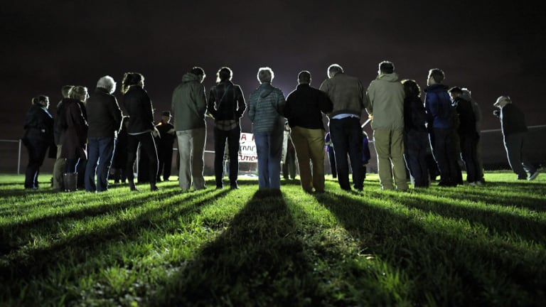 People form a circle and pray against the death penalty before the execution.