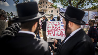 Ultra orthodox Jews stand by supporters of Donald Trump outside the new American embassy in Jerusalem on Monday.