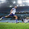 Brendon Wakeham of the Bulldogs kicks in an empty stadium.