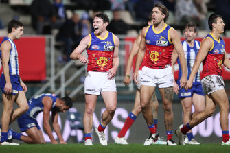 Lachie Neale celebrates with his Lions teammates after kicking a goal against the Kangaroos.