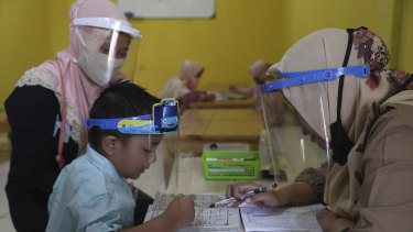 Teachers and students wear protective gear as a precaution against the new coronavirus outbreak during a class at a Quran educational facility at on the outskirts of Jakarta, Indonesia, Wednesday, July 1, 2020.