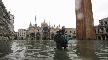 A woman carries her daughter in a flooded St. Mark's Square in Venice on Tuesday.