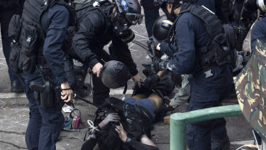 Policemen in riot gear detain a protester who was trying to flee from the Hong Kong Polytechnic University.