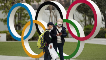 "People check their photos after posing in front of the Olympic rings in Tokyo. Tokyo pitched itself as ""a safe pair of hands"" when it was awarded the Olympics more than seven years ago. The pandemic, however, means, less certainty."