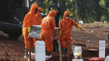 Workers in protective suits carry the coffin of a suspected victim of COVID-19 during a burial at Pondok Ranggon cemetery in Jakarta, Indonesia, earlier this month.