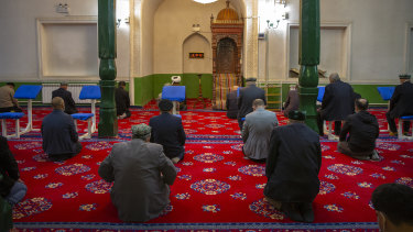 Uyghurs and other members of the faithful pray during services at the Id Kah Mosque in Kashgar in western China's Xinjiang Uyghur Autonomous Region. Outside observers say scores of mosques have been demolished.