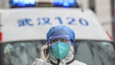 A nurse in protective gear talks on her phone near an ambulance in Wuhan in central China's Hubei Province.