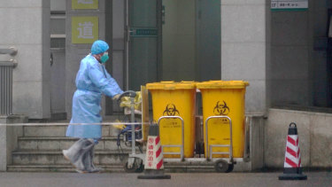 A staff member moves bio-waste containers past the entrance of the Wuhan Medical Treatment Center in Wuhan, China, where some people infected with a new virus are being treated.