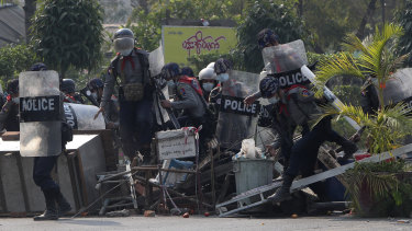 Myanmar riot police with shields approach protesters.