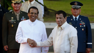 Like-minded: Sri Lanka President Maithripala Sirisena, left, and Philippine President Rodrigo Duterte shake hands in Manila last month.