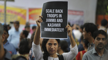 An Indian activist holds a placard during a protest against Indian government revoking Kashmir's special constitutional status in New Delhi on Wednesday.