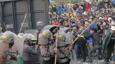 Student protesters throw projectiles at riot police outside the parliament building in Jakarta, Indonesia, on Tuesday.