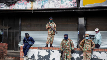 Soldiers stand guard as residents of Alexandra Township begin cleaning up after several days of looting.