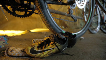 June 25, 2018: A pair of soccer boots lie next to the bicycles of the missing boys at the cave entrance in Chiang Rai, northern Thailand.