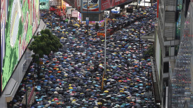 Demonstrators carry umbrellas as they march along a street in Hong Kong.