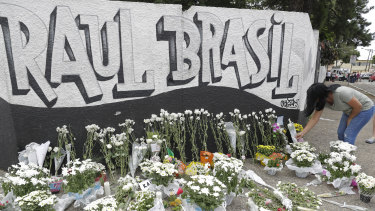 A woman leaves flowers one day after a mass, school shooting outside the Raul Brasil state school in Suzano.