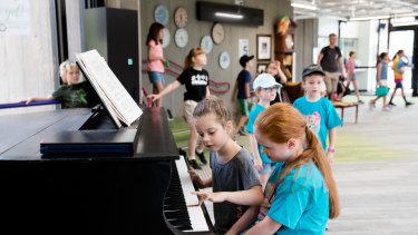 It takes a village: students play a grand piano during lunch time at Lindfield Learning Village.