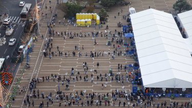 People queue outside a COVID-19 mass vaccination centre at Rabin Square in Tel Aviv.