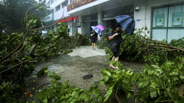 Women holding umbrellas walk by fallen tree branches caused by typhoon Mangkhut in Nanshan District in Shenzhen, south China's Guangdong Province.