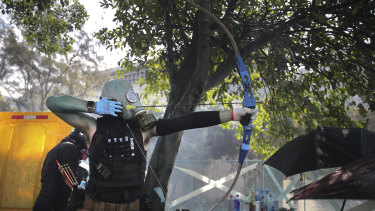 A protester prepares to fire a bow and arrow during a confrontation with police at Hong Kong Polytechnic University.