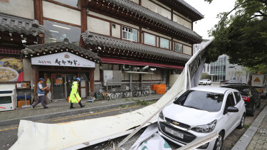 A vehicle is damaged by a fallen sign from a building as Typhoon Lingling brings strong winds and rain to Seoul.