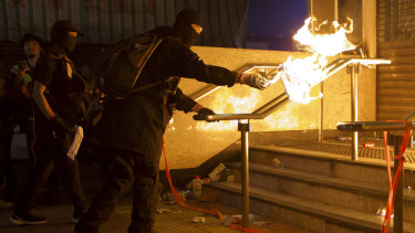 Pro-democracy protesters throw molotov cocktails to an entrance gate of Whampoa MTR station in Hong Kong last week.