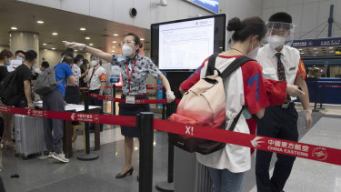 Airline employees directing travellers at the check-in in Beijing: The country's aviation regulator recommends stepping up COVID-19 safety regulations further on board.