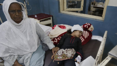 A woman sits next to her injured granddaughter who lies on a bed after the earthquake in Mirpur, in north-east Pakistan.