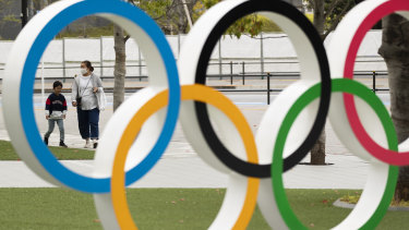 A mother and a boy walk by a display of the Olympic rings at the Japan Olympic Museum in Tokyo.