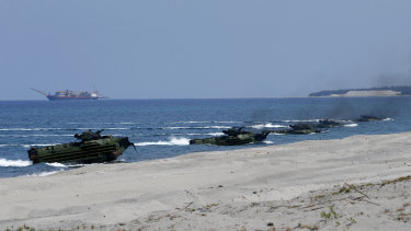 Amphibious assault vehicles carrying American and Philippine troops make a beach landing during a military exercise in the Philippines last year.