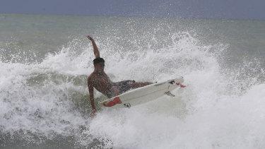 Abu Dzar Al-Ghifari surfs at Carita beach, Indonesia, despite the expanded exclusion zone.