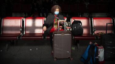 A traveller wears a face mask as she sits in a waiting room at a Beijing railway station. Cases of the virus have been confirmed in Beijing.