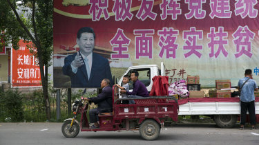 """Chinese President Xi Jinping and part of a slogan that reads """"Actively play the leading role of party building and comprehensively implement the plan for poverty alleviation"""" near Pingdingshan city in Henan province."""