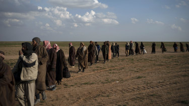 Men walk to be screened by US-backed Syrian Democratic Forces  fighters after being evacuated  near Baghouz, in eastern Syria. The number of people in the area has surpassed earlier estimates.