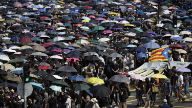 Protesters hold umbrellas as they march in Hong Kong earlier this month.