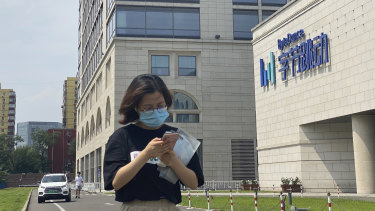 A woman uses her phone as she passes by the ByteDance headquarters in Beijing, China.