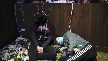 Pro-democracy protesters take a nap while charging their devices inside the campus of the Hong Kong Baptist University in Hong Kong.