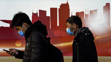 People wearing face masks to help curb the spread of the coronavirus walk by a mural depicting China's skyscrapers along a street in Beijing.