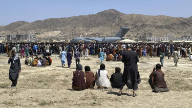 Hundreds of people gather near a US Air Force C-17 transport plane along the perimeter at the international airport in Kabul, Afghanistan.