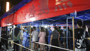 People line up for COVID-19 tests at a testing station in Nanjing in eastern China's Jiangsu Province.