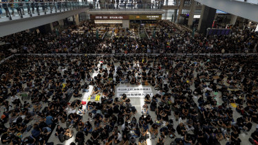 China's efforts to depict the protests as small and violent are at odds with reality. Here, hundreds of protesters stage a peaceful sit-in at the Hong Kong airport on Monday.