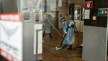 Cleaners wearing protective equipment disinfect the Holiday Inn quarantine hotel at Melbourne Airport this week.