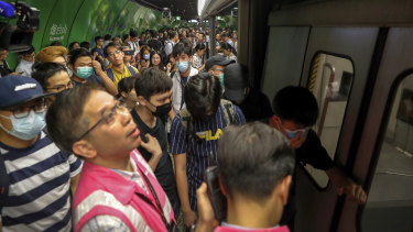 Protesters snarl the morning rush by blocking train doors at Fortress Hill MTR station in Hong Kong on Monday.