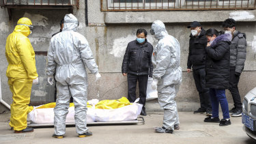 Funeral home workers remove the body of a person suspected to have died from the coronavirus outbreak from a residential building in Wuhan in February.