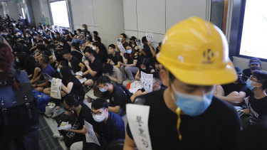 Demonstrators sit during a protest at the Yuen Long MTR station, where demonstrators and others were violently attacked by men in white T-shirts following an earlier protest in July.