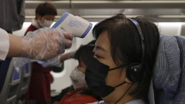 Stewardesses take temperatures of passengers as a preventive measure for the coronavirus on an Air China flight from Melbourne to Beijing.